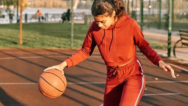 フィールドでバスケットボールをしている女性