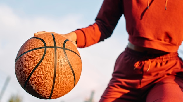 屋外でバスケットボールをする女性