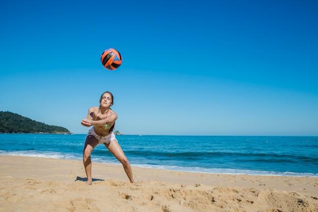 ビーチでビーチ・ボレーをしている女性