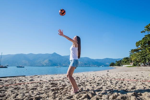 Женщина играет в пляжный волейбол