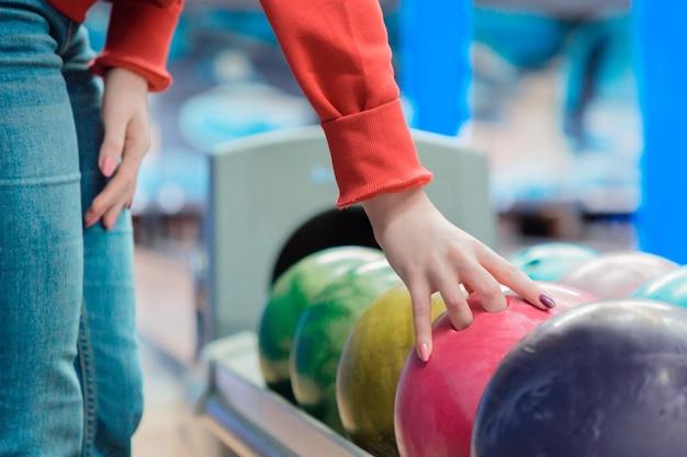 Женщина играет в боулинг в спортивном клубе.