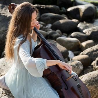 岩と海のそばでチェロを演奏する女性