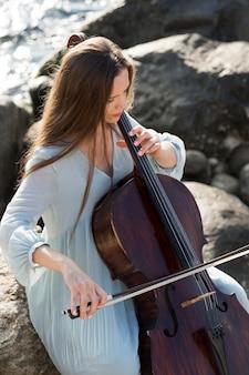 Женщина играет на виолончели у океана