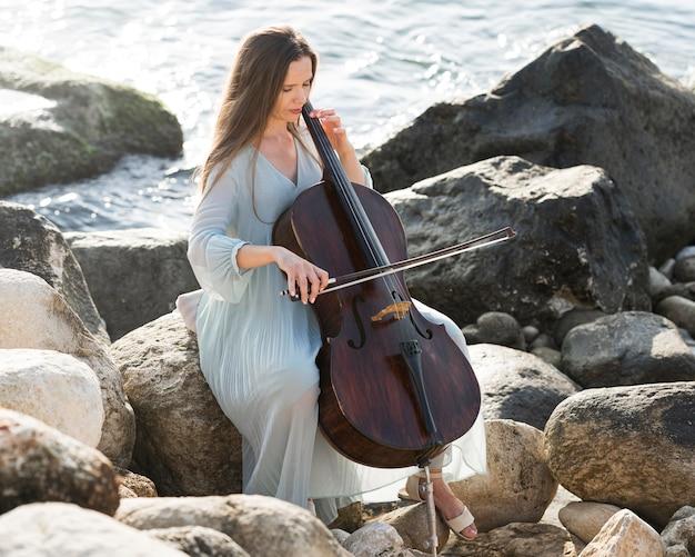 海でチェロを弾く女性