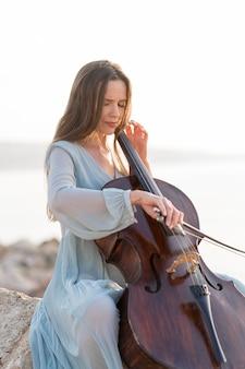 야외에서 바위에 첼로 연주하는 여자