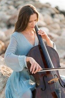 Женщина играет на виолончели на скалах