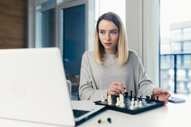 Женщина играет в шахматы онлайн использует ноутбук