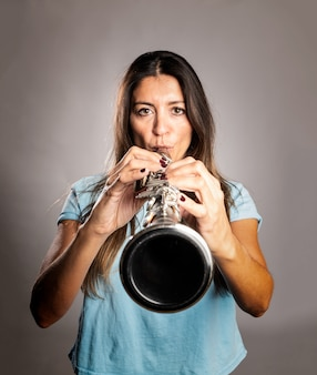 Woman playing a clarinet on gray
