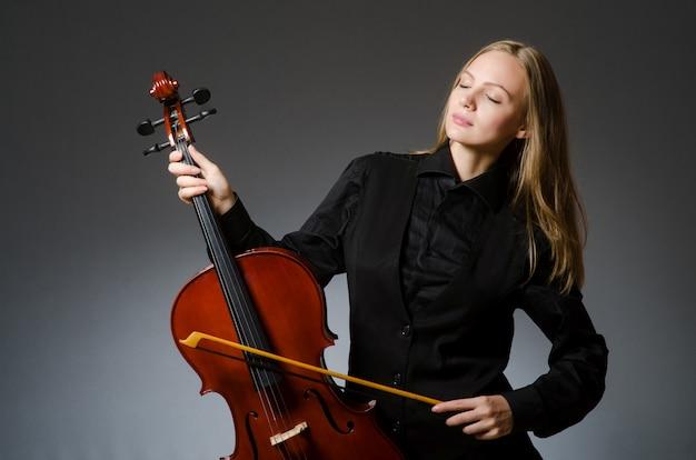 Женщина играет классическая виолончель в музыкальной концепции