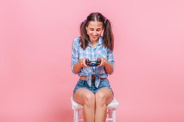 ピンクの壁にジョイスティックでコンピューターゲームをしている女性