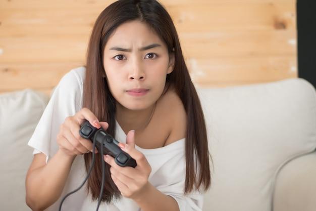 コンソールビデオゲームをプレイする女性