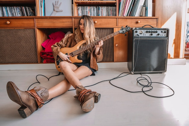 Woman playing electric guitar on floor