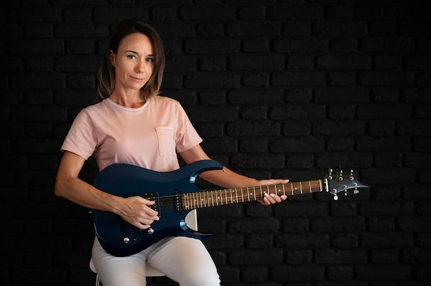 Woman playing an electric guitar at home