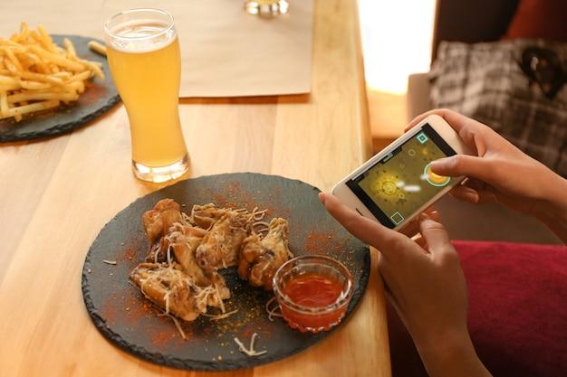 カフェ、クローズアップでおいしいバーベキューの翼を持つテーブルでスマートフォンを使用してゲームをしている女性