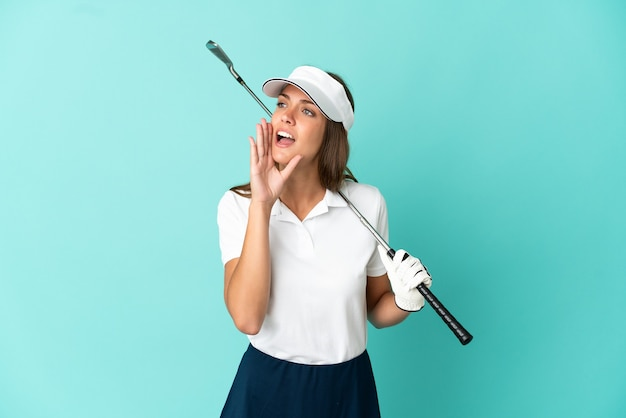 Woman playing golf over isolated blue background shouting with mouth wide open to the side