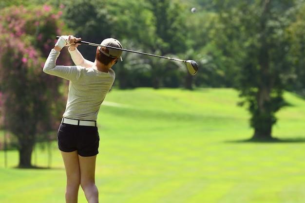 Женщина играет в гольф на красивом естественном поле для гольфа
