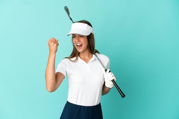 勝利を祝う孤立した青い背景の上でゴルフをしている女性