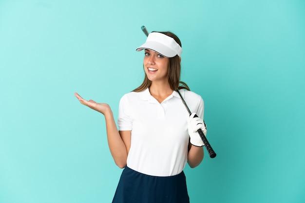 孤立した青い背景の上でゴルフをしている女性は、来て招待するために手を横に伸ばします