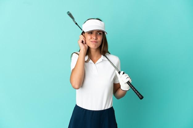 고립 된 파란색 배경 위에 골프를 치는 여자는 좌절과 귀를 덮고