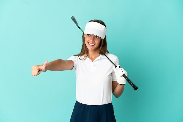 제스처를 엄지 손가락을주는 고립 된 파란색 배경 위에 골프를하는 여자