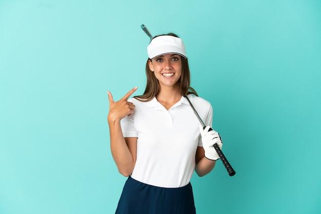 Женщина играет в гольф на изолированном синем фоне, показывая большой палец вверх
