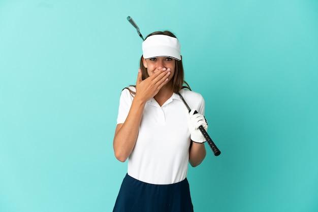 Женщина играет в гольф на изолированном синем фоне, счастливая и улыбающаяся, прикрывая рот рукой