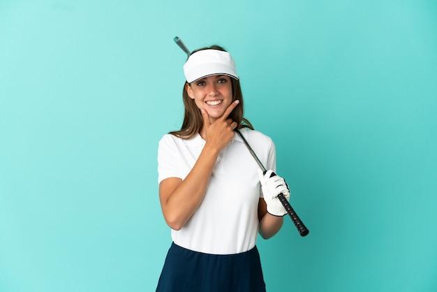 Женщина играет в гольф на изолированном синем фоне счастлива и улыбается