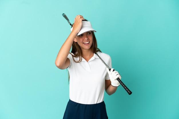 격리 된 파란색 배경 위에 골프를 치는 여자는 뭔가를 실현하고 해결책을 계획하고 있습니다.