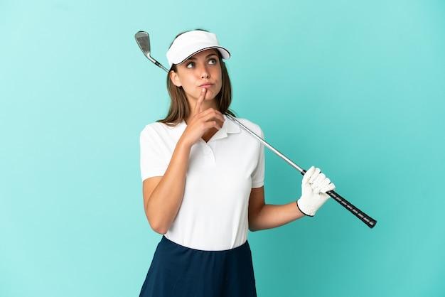 見上げている間疑いを持っている孤立した青い背景の上でゴルフをしている女性