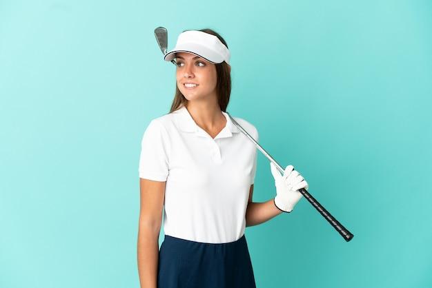 Женщина играет в гольф на изолированном синем фоне, глядя в сторону