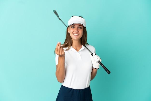 Женщина играет в гольф на изолированном синем фоне, делая денежный жест