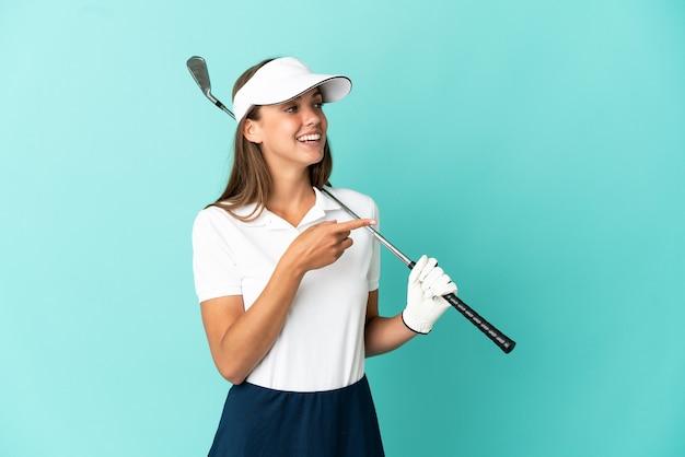측면에 손가락을 가리키고 제품을 제시하는 격리 된 파란색 배경 위에 골프를하는 여자
