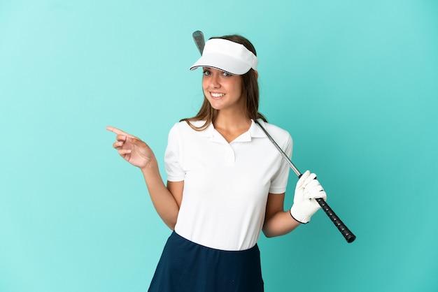 Женщина играет в гольф на изолированном синем фоне, указывая пальцем в сторону