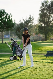 Woman playing golf on sunny day with her wheeled golf clubs bag. female about to hit the ball with iron club on a beautiful golf course.