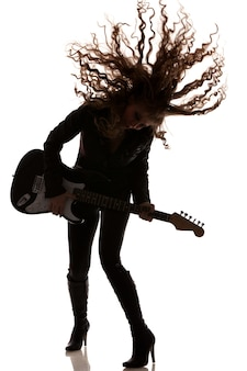 Woman playing on guitar and dancing, waving her hair. full length photo isolated on white background