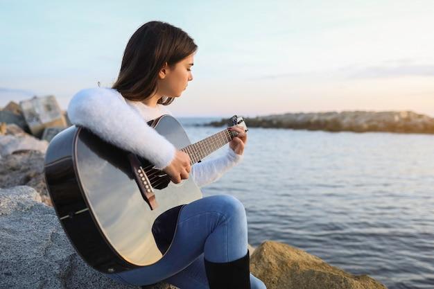 海の前でギターを弾く女性