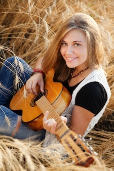 Woman playing the guitar in a wheat field