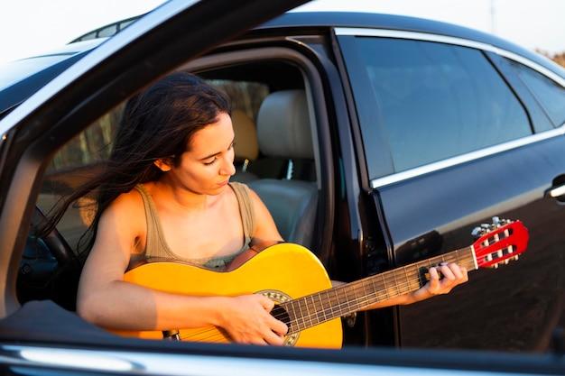 彼女の車の座席にいる間ギターを弾く女性