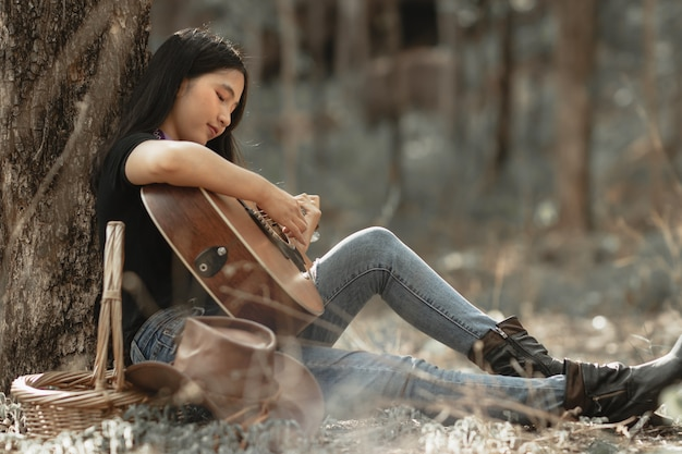 Woman playing the guitar with happy in the forest.