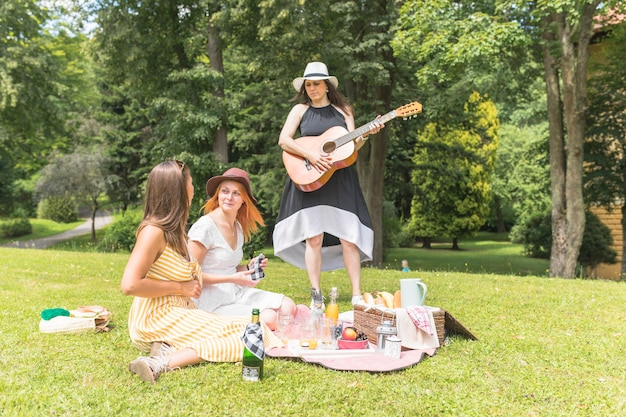 Woman playing guitar with her friends enjoying in the picnic