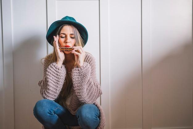Donna che gioca armonica vicino al muro bianco