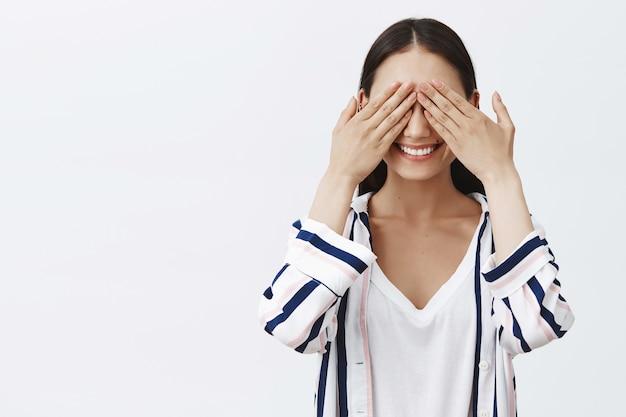 かくれんぼをしている女性。ストライプのブラウスにスリル満点の格好良いスタイリッシュな女性、手のひらで目を覆い、興味をそそる表情で笑顔、驚きを待っています