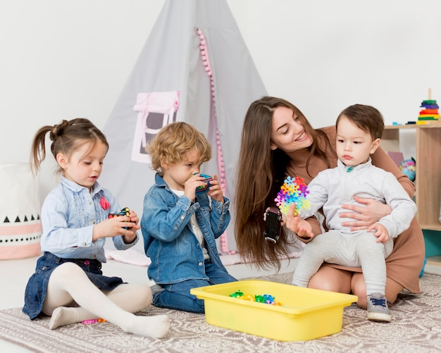 Woman playing at home with children and toys