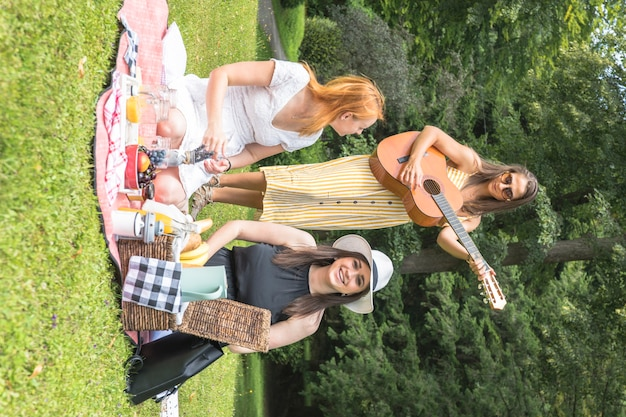 Woman playing music on guitar with her friends enjoying in the picnic