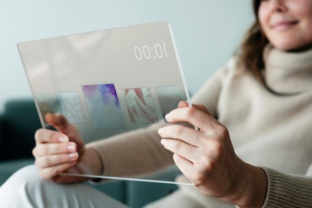 透明なタブレットの革新的な技術で音楽を演奏する女性