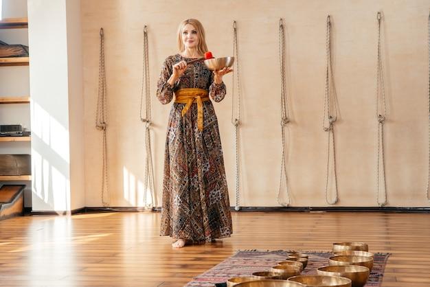 Женщина играет на тибетской поющей чаше для звуковой терапии