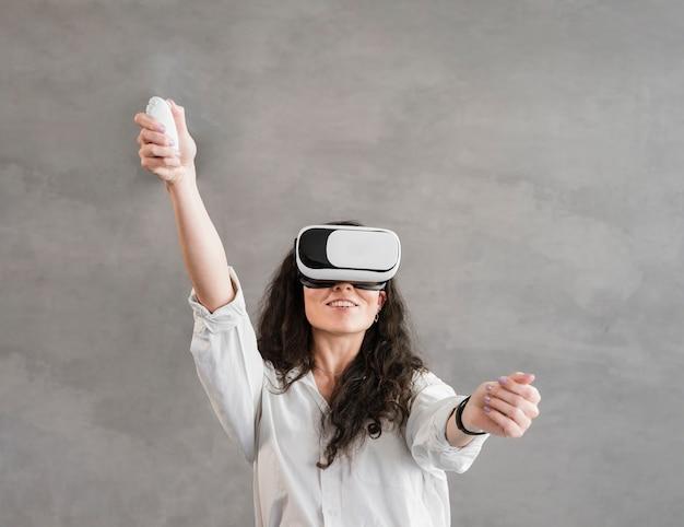 Женщина играет на виртуальной реальности в современной минималистской комнате