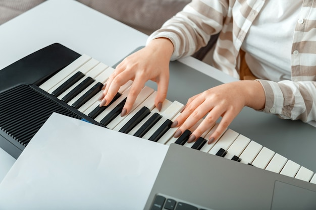Женщина играет пианино записывает музыку на синтезаторе, используя примечания и ноутбук. женские руки музыкант-пианист совершенствует навыки игры на фортепиано. музыкальное образование онлайн по хобби вокал, пение на фортепиано.