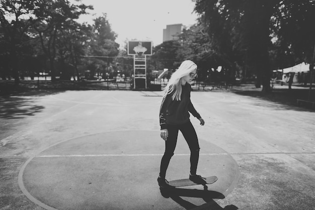 Woman playing skateboard in basketball court