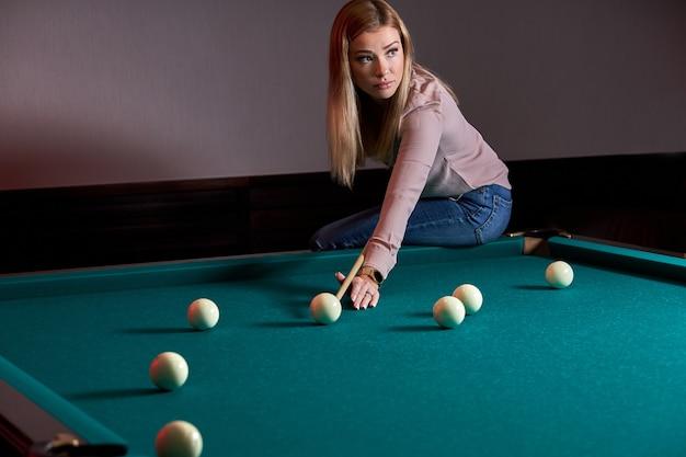 Женщина играет в снукер, готовится стрелять шарами для пула на бильярдном столе, сидя на нем
